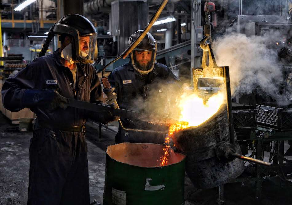 Foundry workers pouring liquid metal